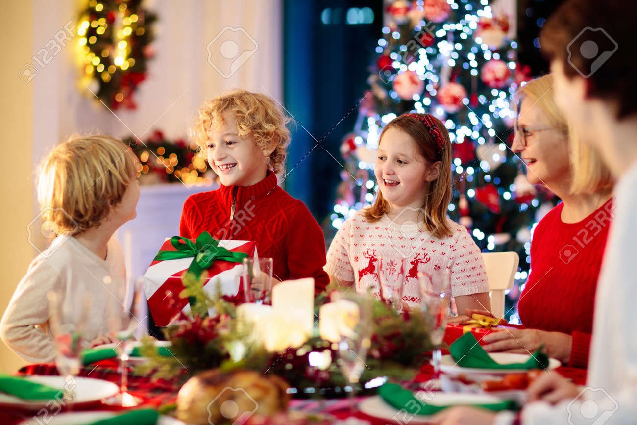 Family with children eating Christmas dinner at fireplace and decorated Xmas tree. Parents and kids enjoy festive meal. Winter holidays celebration and food. Grandmother cooking roasted turkey. - 159510024