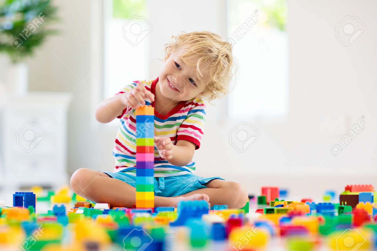 Child playing with colorful toy blocks. Little boy building tower at home or day care. Educational toys for young children. Construction block for baby or toddler kid. Mess in kindergarten play room. - 167742777