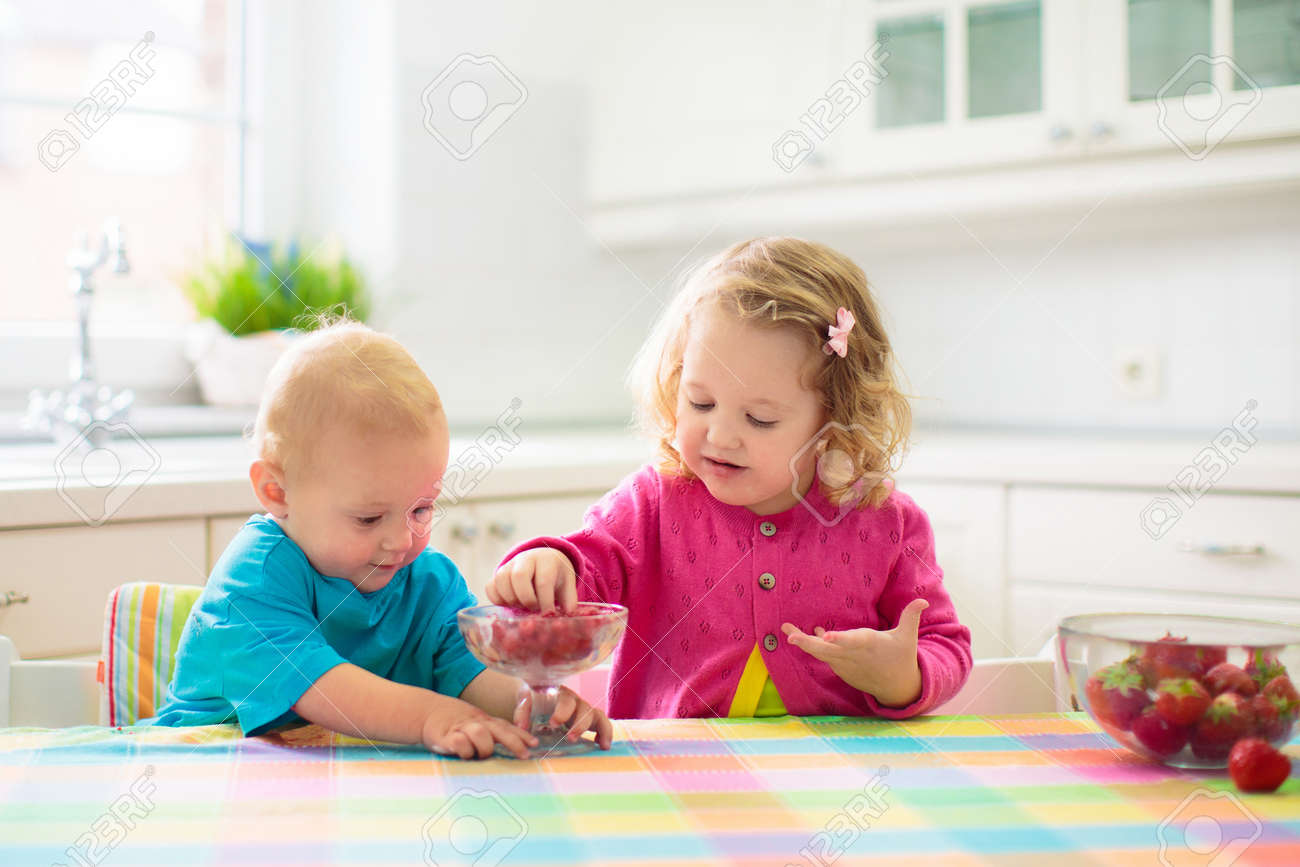 Child having breakfast. Kid drinking milk and eating cereal with fruit. Little boy and girl at white dining table in kitchen at window. Kids eat on sunny morning. Healthy balanced nutrition for kids. - 168267806