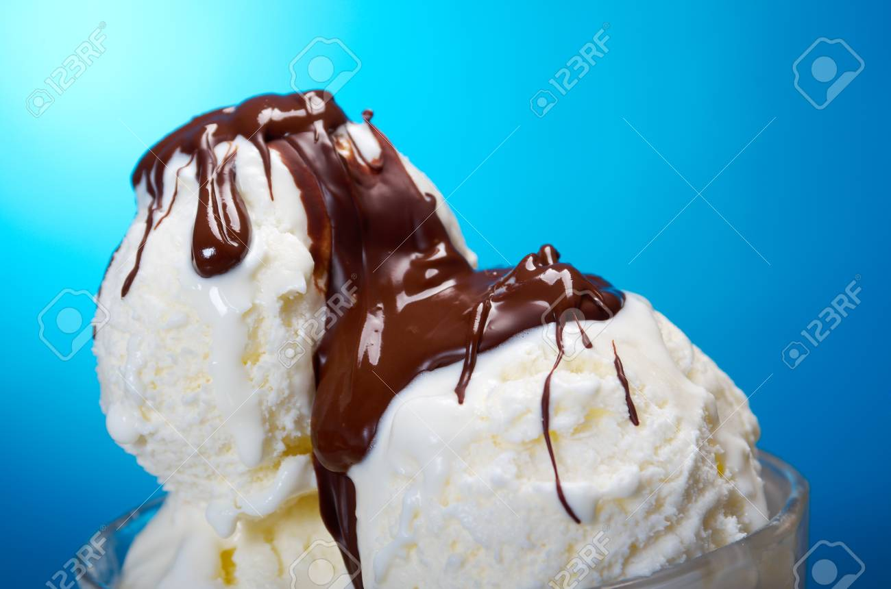 ice cream in with chocolate sauce  closeup  on blue background Stock Photo - 18013872