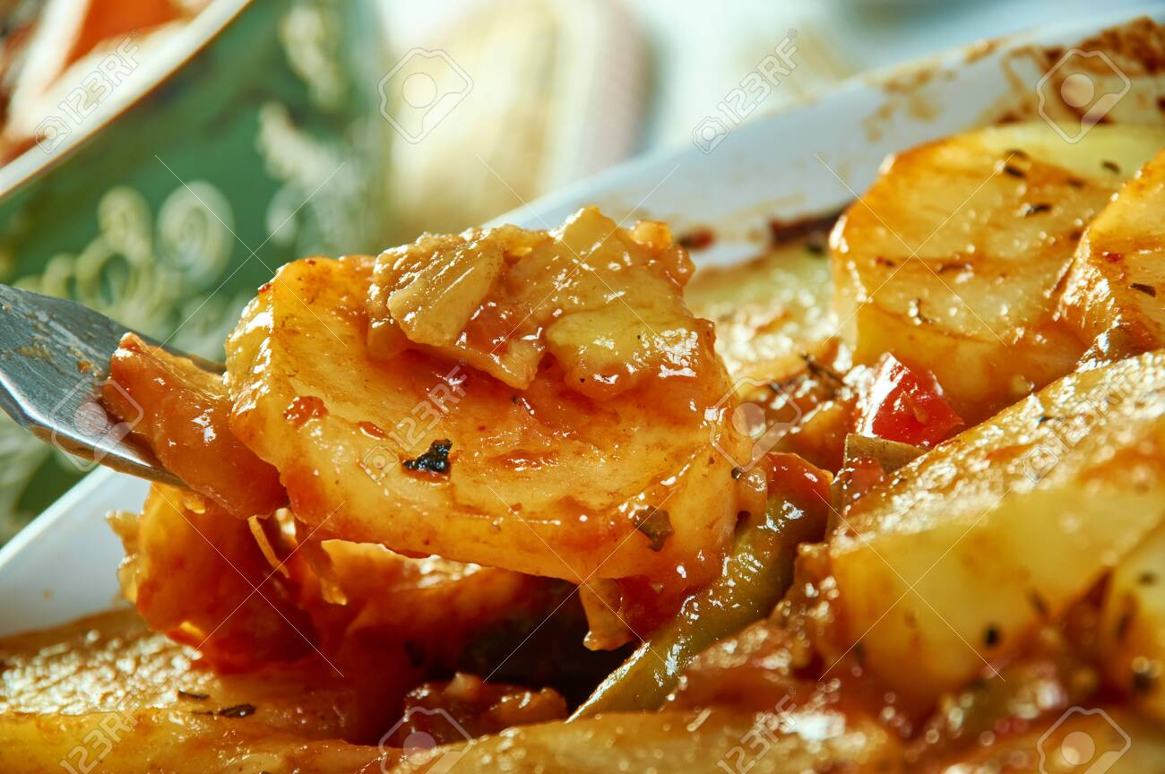 Tumbet - traditional vegetable dish from Majorca, combines layers of sliced potatoes, aubergines and red bell peppers - 127455657