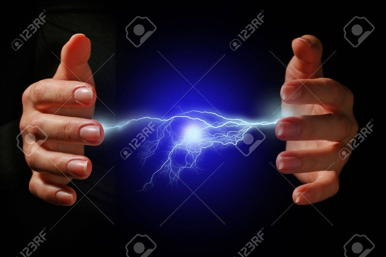 Hands and electric discharge over black background. Stock Photo - 8848695