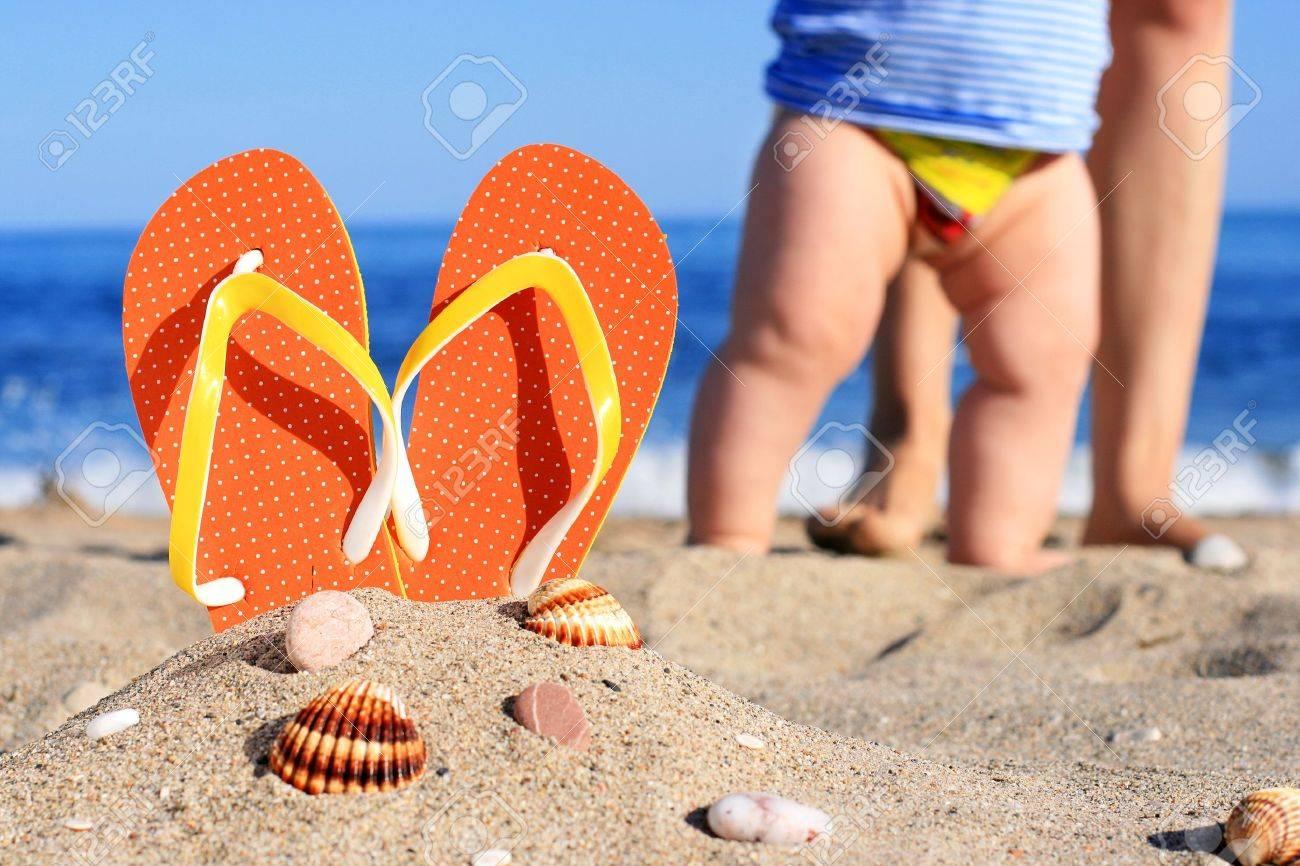 Orange flip-flops in sand on the beach in Barcelona Stock Photo - 19696078