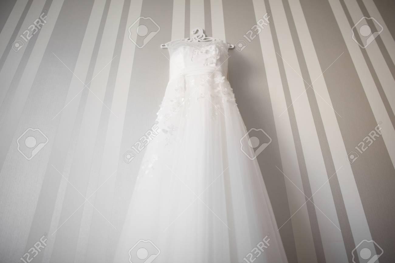 43493fc6fb59 Bellissimo abito da sposa appeso al muro Archivio Fotografico - 54673232