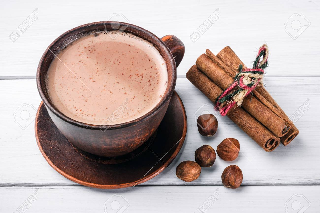 Hot cocoa with milk in brown clay cup, hazelnut and cinnamon sticks on table of white wooden planks. - 88287235