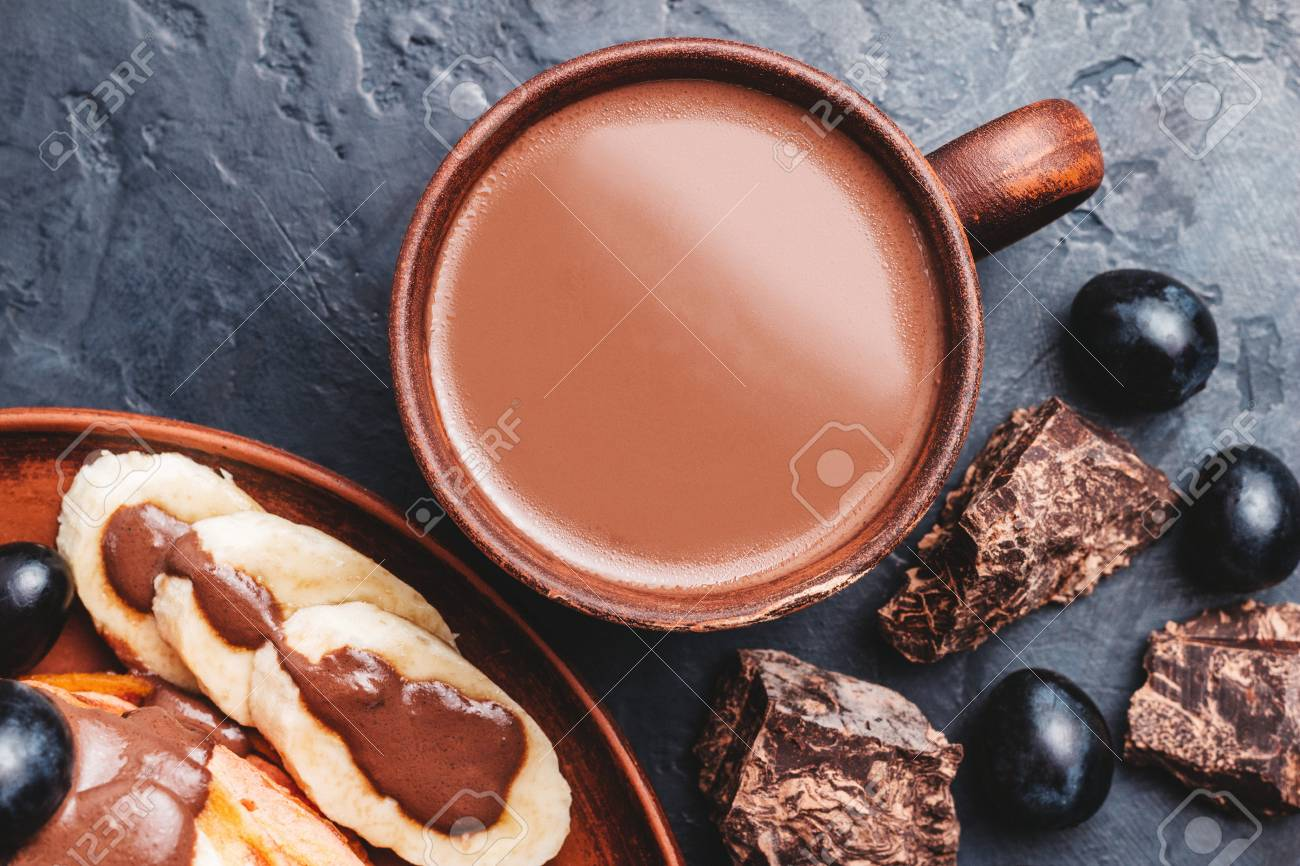 Hot chocolate drink in a cup and pancakes with banana, chocolate sauce and grapes in plate, on dark background, top view. - 118957170