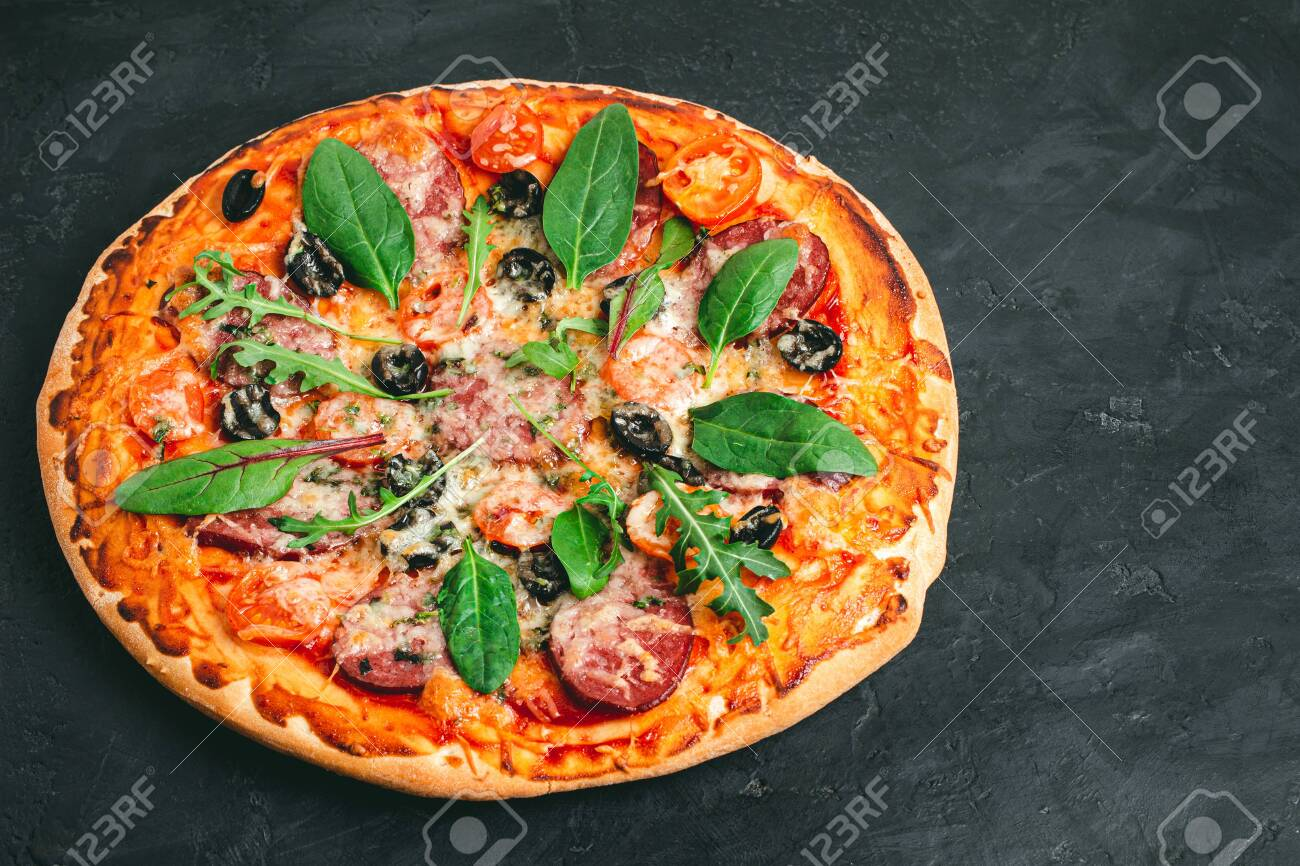Homemade baked pizza margarita with salami, mozzarella cheese, olives and green leaves. - 140209686