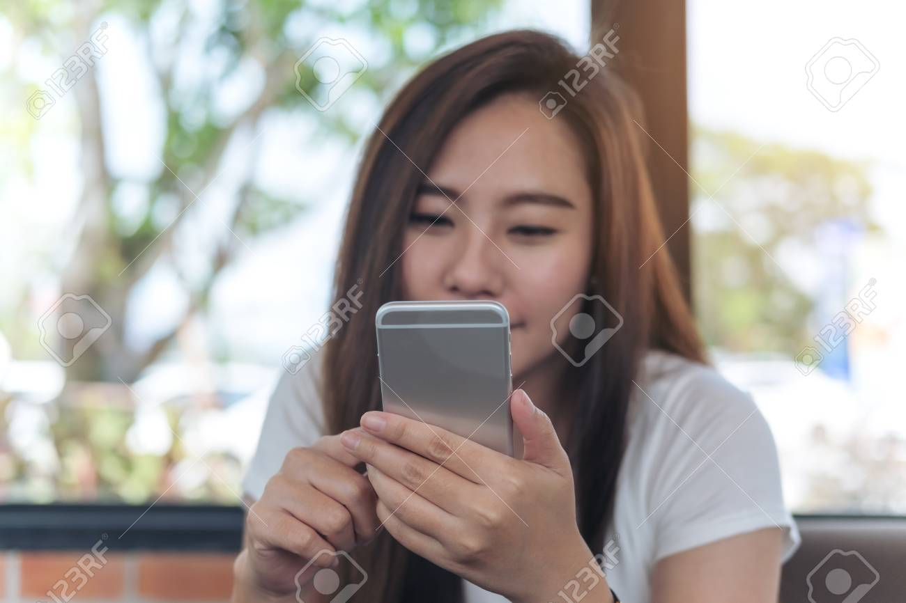 A beautiful Asian girl with smiley face holding and using smart phone in  coffee shop Stock