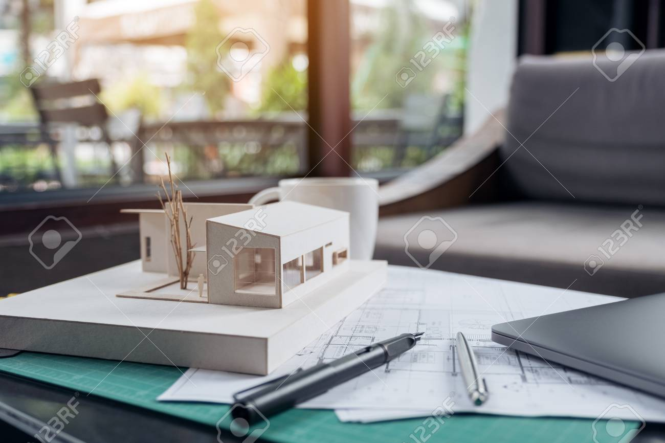 An architects designed architecture model with shop drawing paper and laptop  on table Stock Photo -