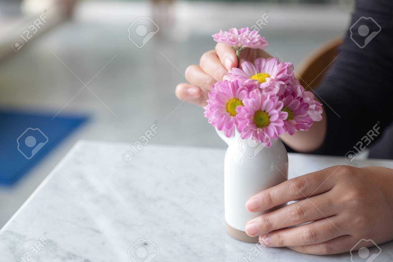 A Woman Arranging Beautiful Pink Flowers In A White Small Vase On