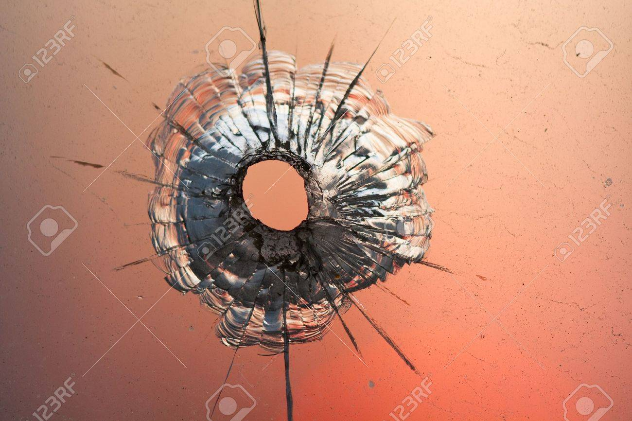 bullet hole in window on the background sunset sky - 9464131