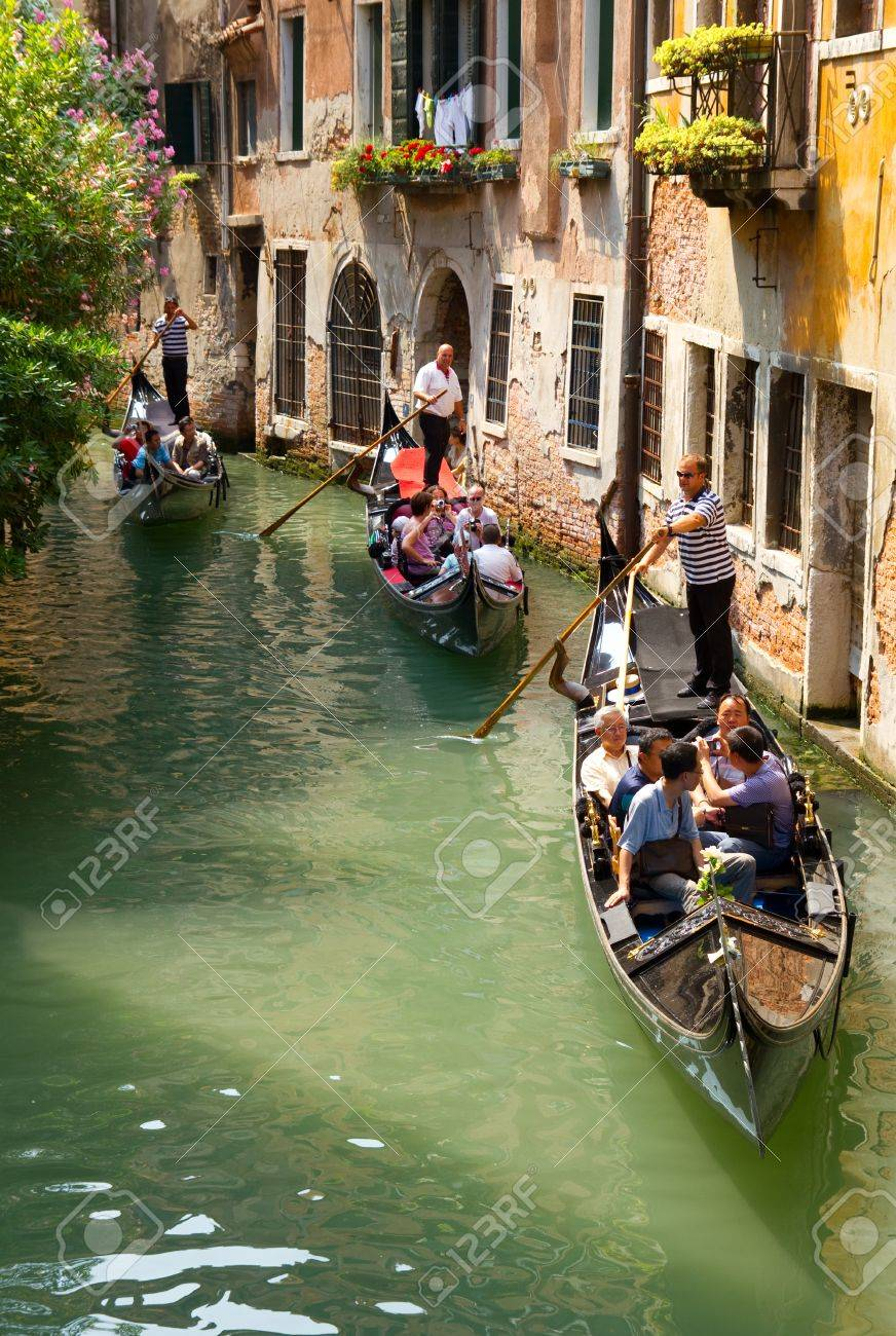 VENICE, ITALY - JUNE 12: Tourists travel  on gondolas at canal near a bridge on June 12, 2010 in Venice, Italy .  The gondola is a traditional, flat-bottomed Venetian rowing boat, well suited to the conditions.  Stock Photo - 12272420