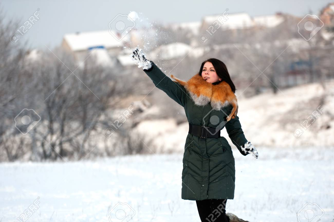 Young woman highly throws a snowball Stock Photo - 12064269