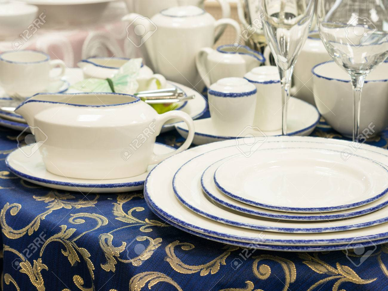 Set of new dishes on table with blue tablecloth. Stack of plates saucer and & Set Of New Dishes On Table With Blue Tablecloth. Stack Of Plates ...