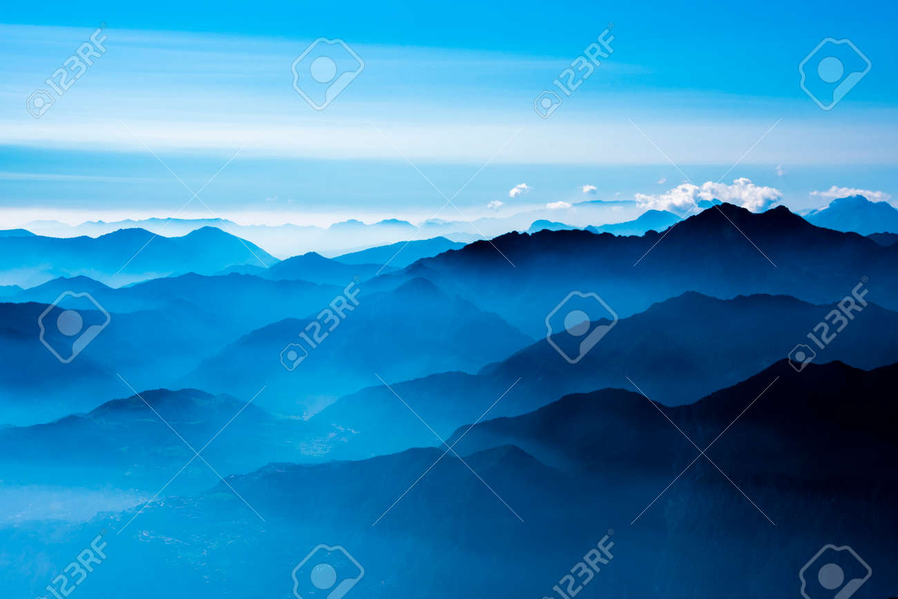 the peaks of the Alps around Lake Garda surrounded by fog with blue sky seen from Monte Altissimo, Trento, Italy - 156362241