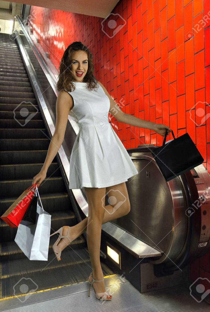portrait of a young sexy woman with shopping bags at fashion mall escslator Stock Photo - 24704528