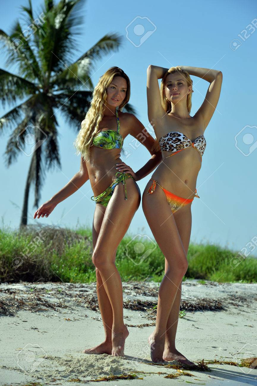 c36c4567930 Two bikini models posing sexy in front of palm tree at tropical beach  location Stock Photo