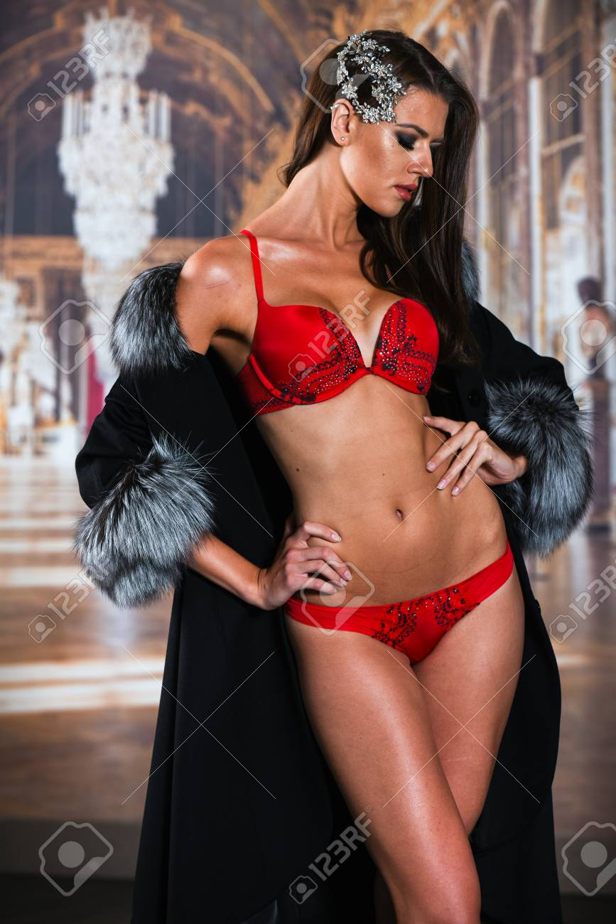 1a2515229 Beautiful sexy woman in red lingerie and luxury fur coat posing over  wallpaper background. Stock