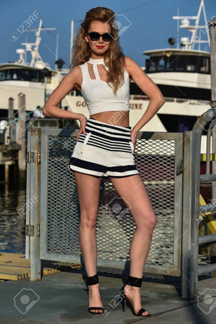 ab33ae37ac Banque d'images - Jolie élégante jeune femme en short marin, haut et  lunettes de soleil posant joli sur la jetée de bateau de plaisance avec  navire sur le ...