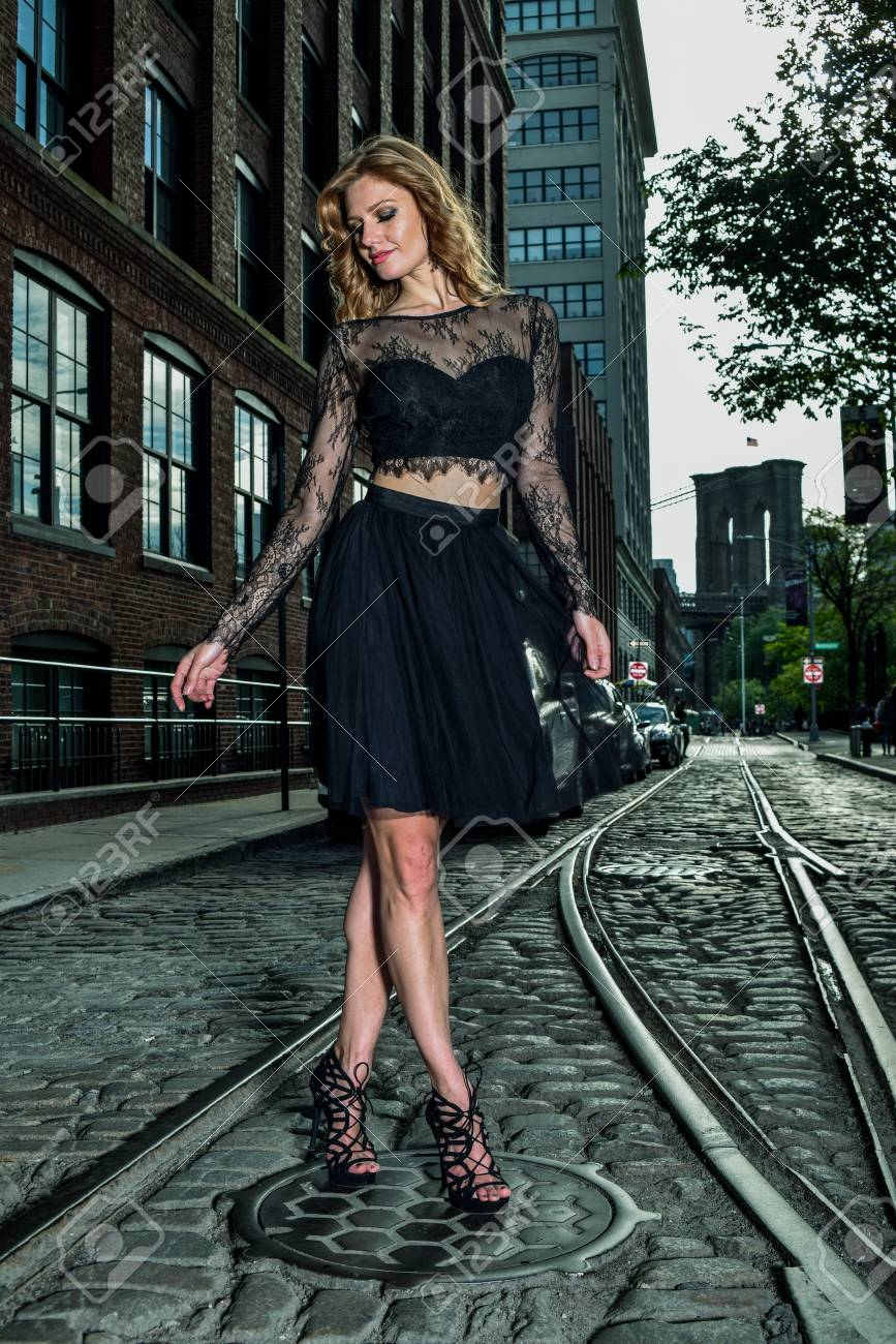manhattan designers mobel Stock Photo - Young beautiful model posing in elegant designers clothes at  historical area under Manhattan bridge at Dumbo area in Brooklyn NY.
