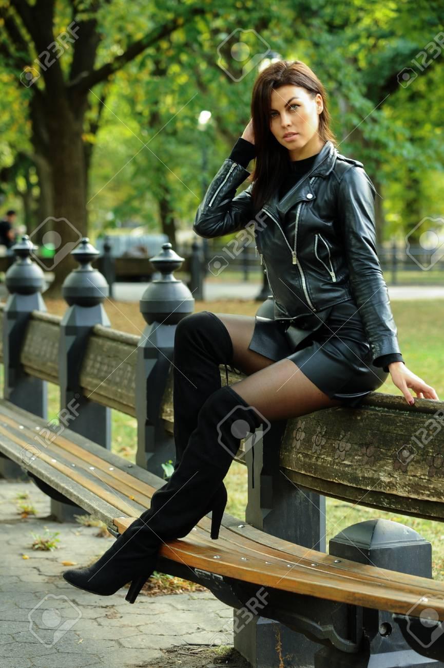 Banque d\u0027images , Séduisante jeune femme portant une veste en cuir, une mini ,jupe et des bottes au,dessus du genou posant au parc en automne.
