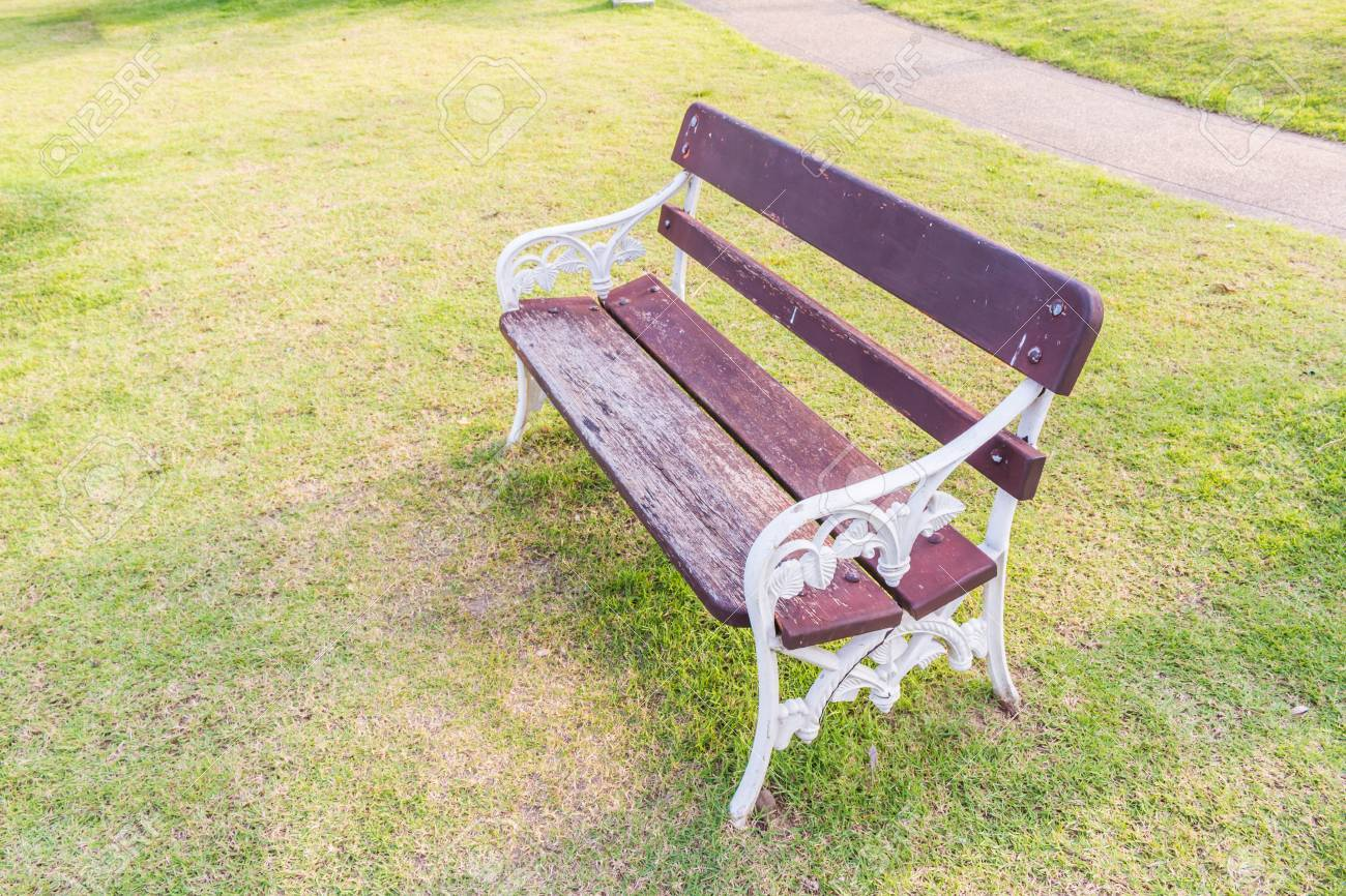Stock Photo   White Chair In The Park On Green Grass Background