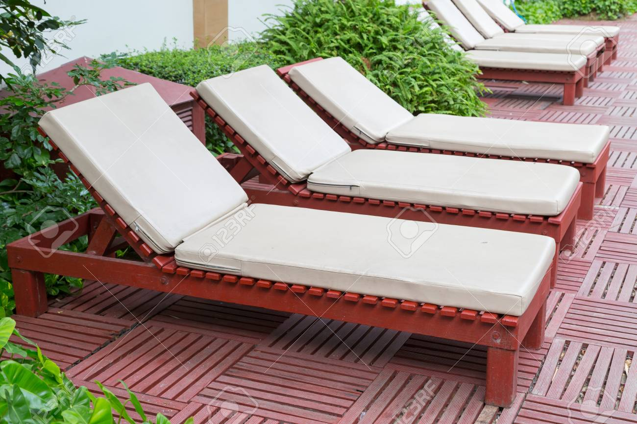Pool chairs near swimming pool with tree background