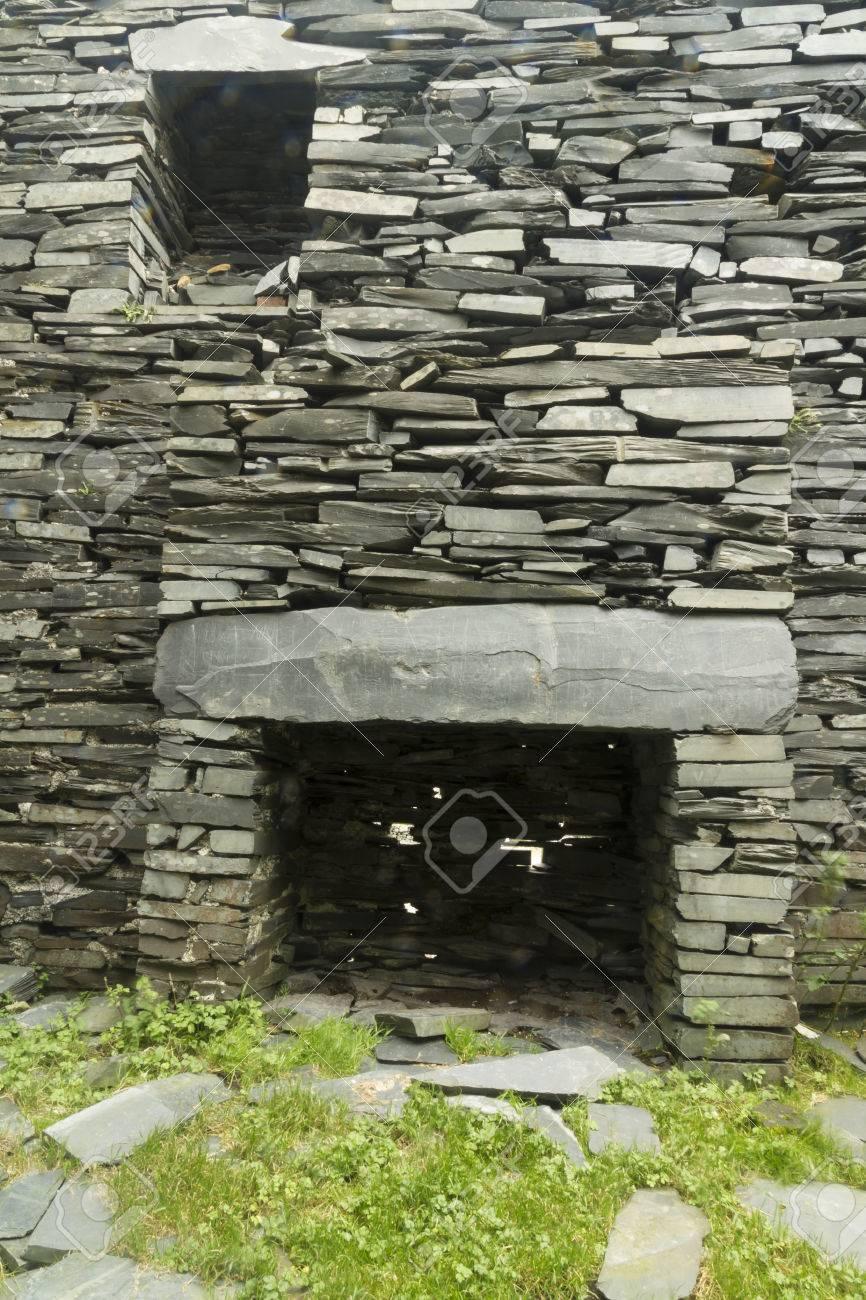 Een open haard in een ruïne, met een droge stenen leistenen muren ...
