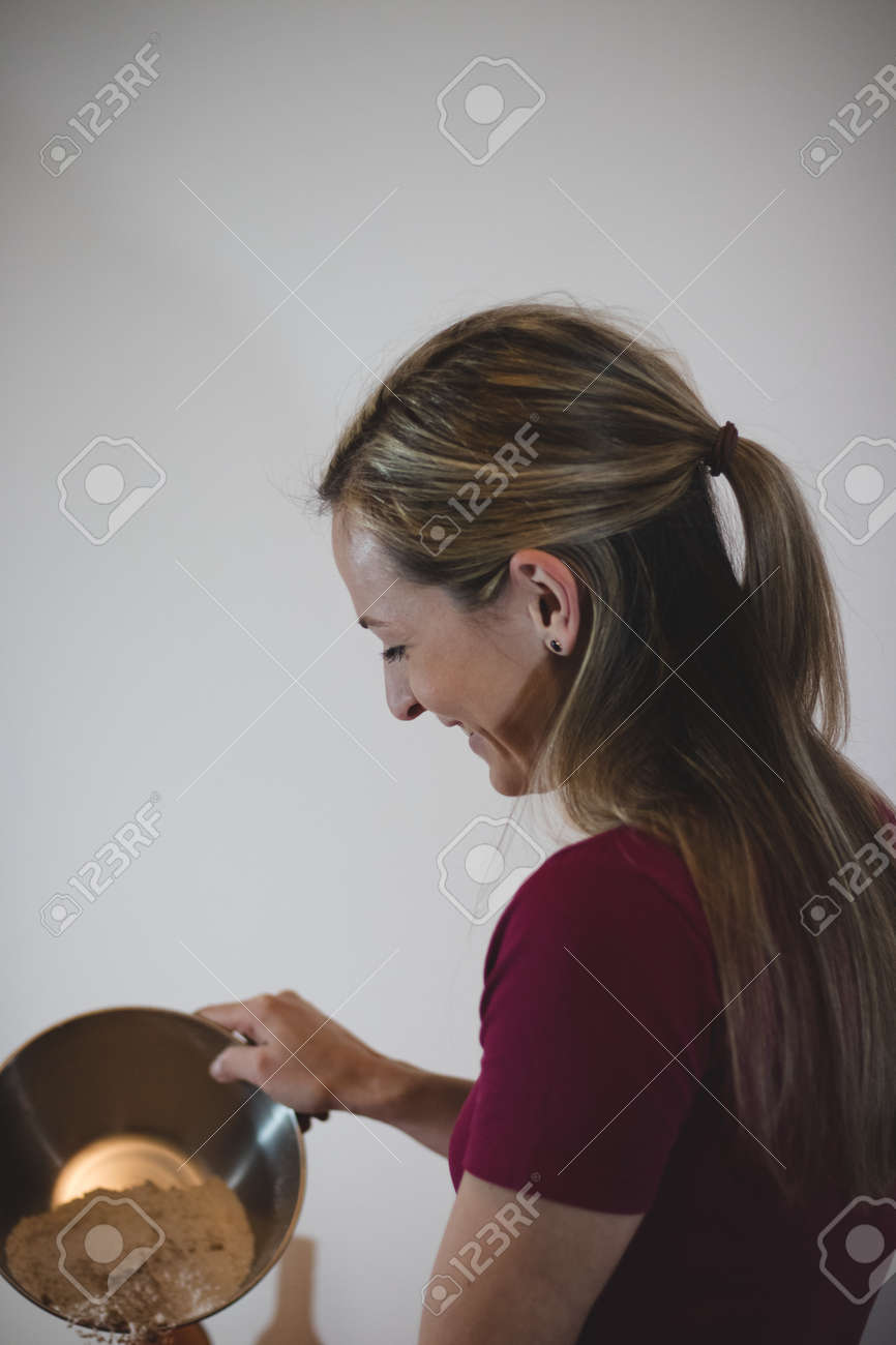 rear view of a woman laughing at her work. A middle-aged woman of evorpian ethnicity is adding more flour to the gingerbread dough for Christmas dinner. Girl with braid and wine t-shirt on white wall- - 160681221