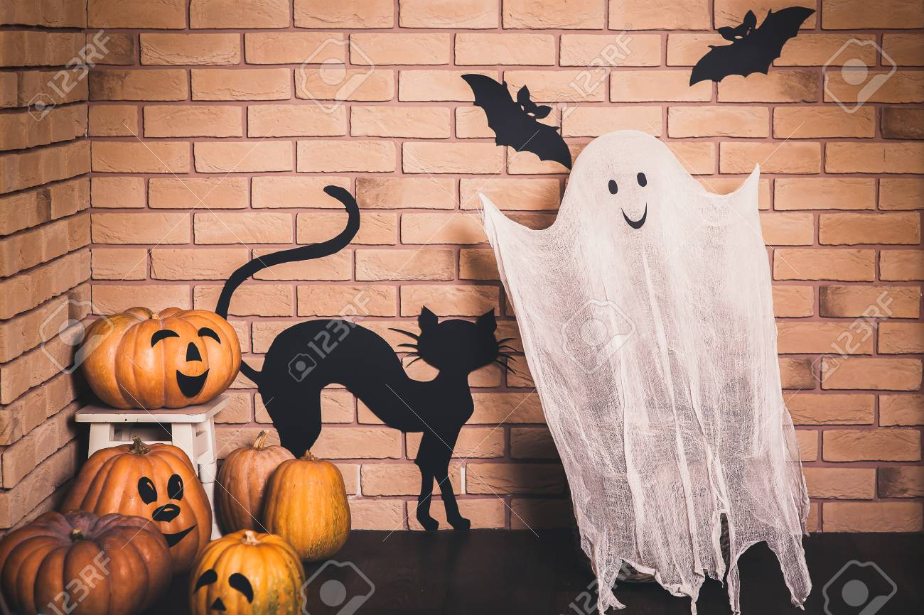 funny halloween decoration with smiling ghost and pumpkins, black