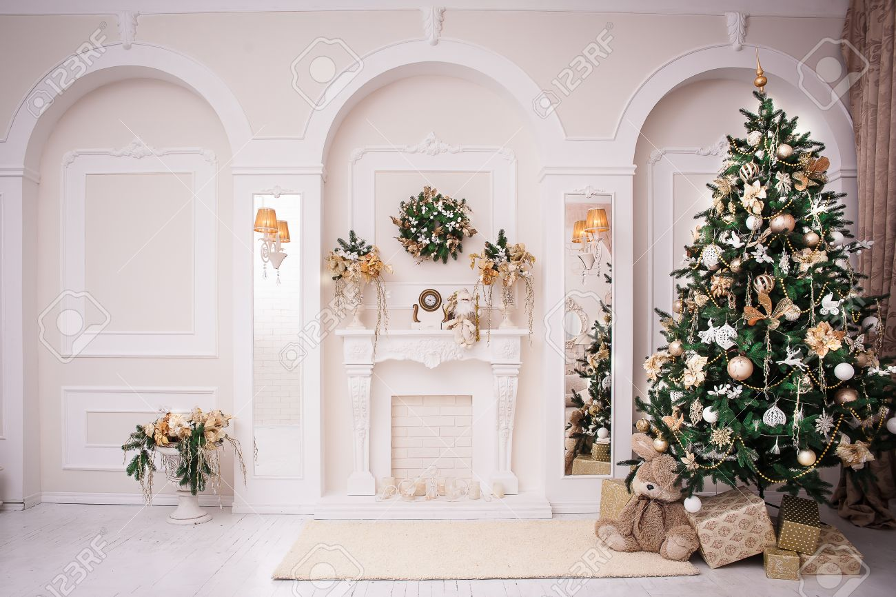 Majestic white hall with classical fireplace arches and mirrors at the wall hanging christmas