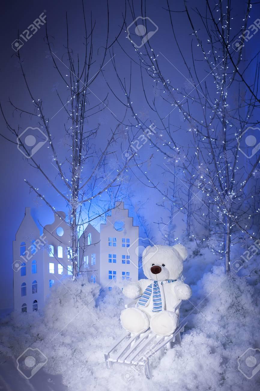 Fondo De Navidad El Oso De Peluche Se Sienta En Trineo Decoración De Nieve Con árboles De Plata Y Pequeñas Casas Con Fondo Azul