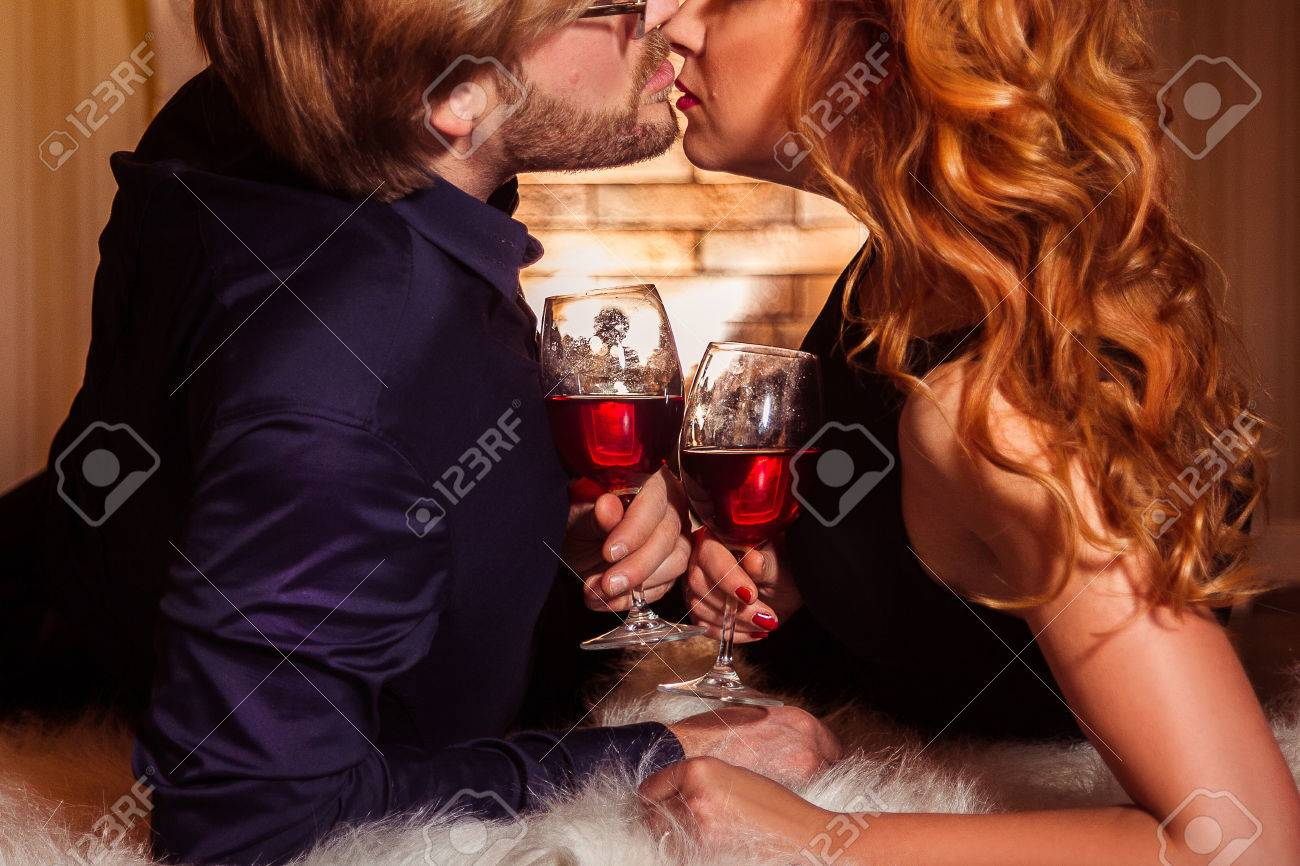 couple relaxing with glass of red wine at romantic fireplace