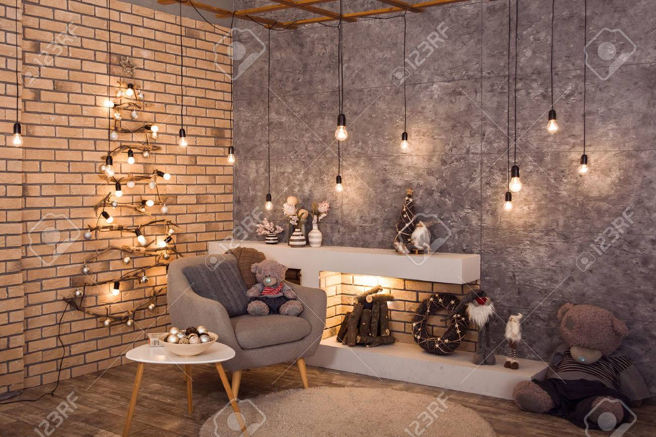 Winter loft style room decorated with original woden Christmas tree, bulbs light garland. Firewood are burning in contemporary scandinavian fireplace. Horizontal - 66707125