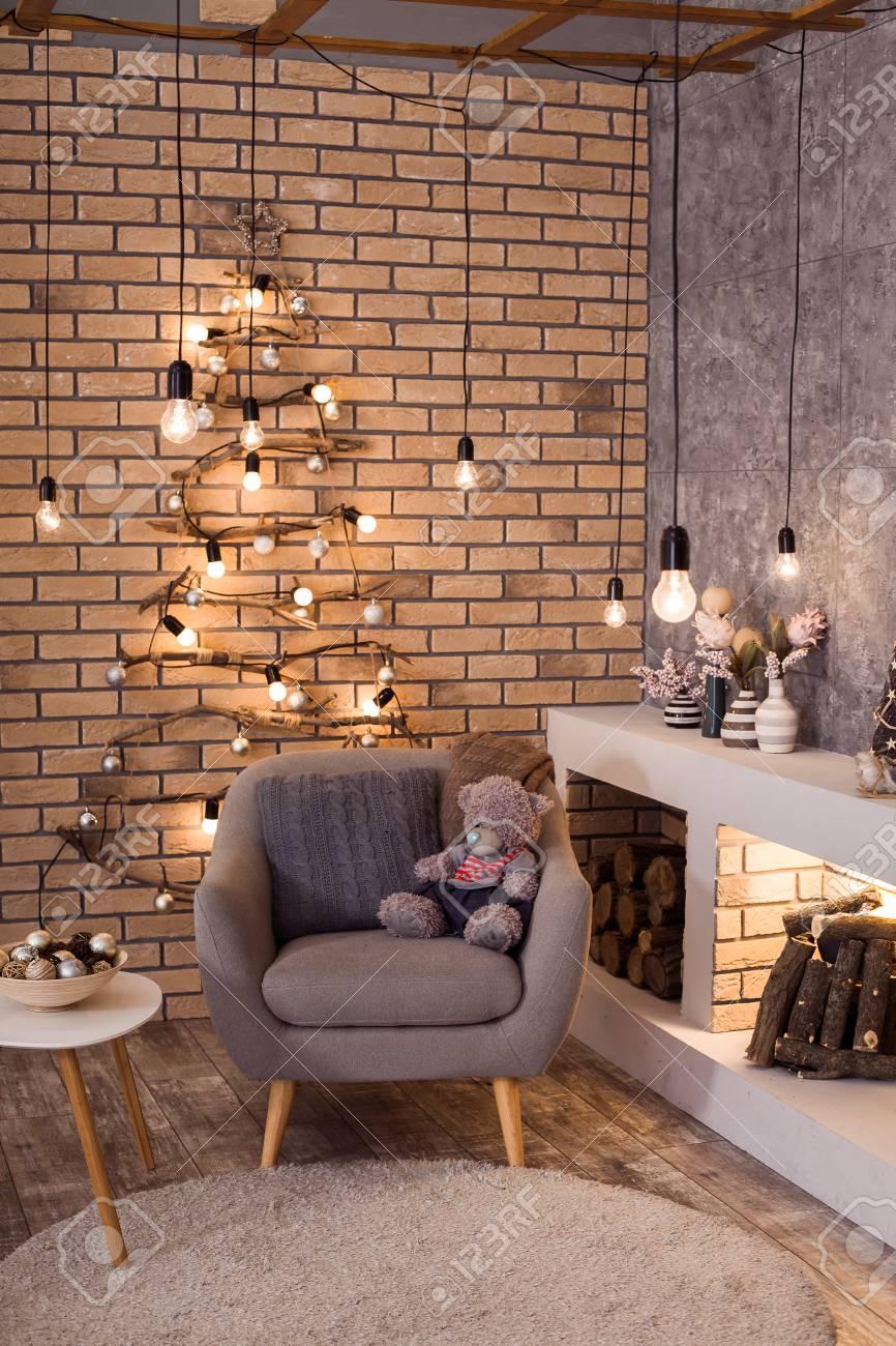 Intérieur contemporain du salon. Sapin de Noël, cheminée moderne et grand  fauteuil gris dans un appartement design loft.