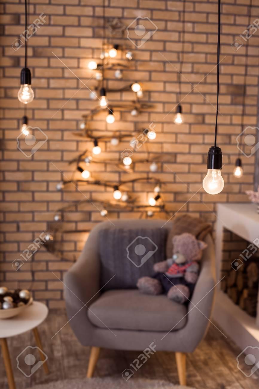 Intérieur moderne du salon. Sapin de Noël créatif, cheminée contemporaine  et grand fauteuil gris dans un appartement design loft.