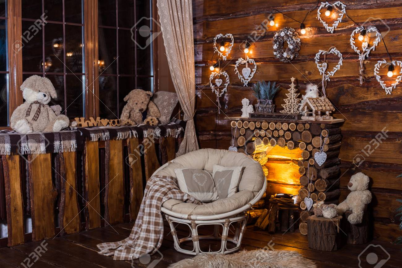 Stock Photo   Wooden Decorative Fireplace, Papasan Chair And Romantic Bulbs  Light In Holiday Rural Living Room.