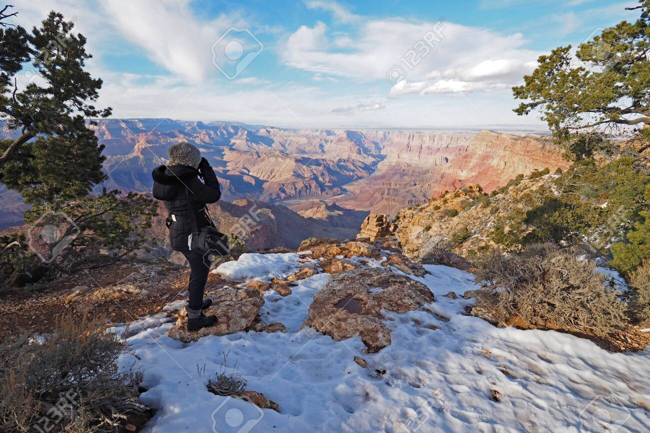 Woman Photographing The Canyon From The South Rim Trail In Grand