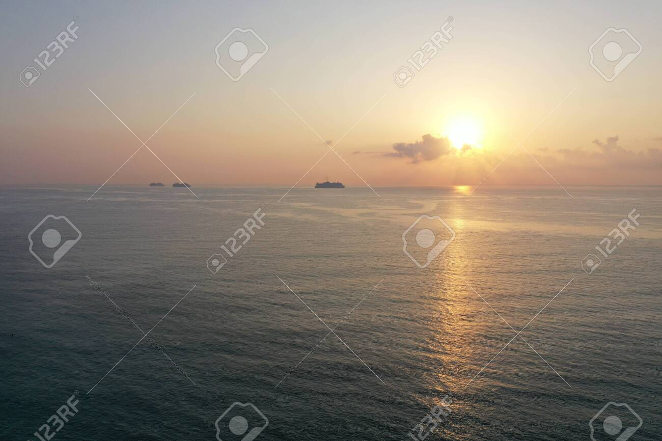 Aerial view of sunrise over ocean from Miami Beach, Florida with cruise ships at anchor on horizon. - 148855615