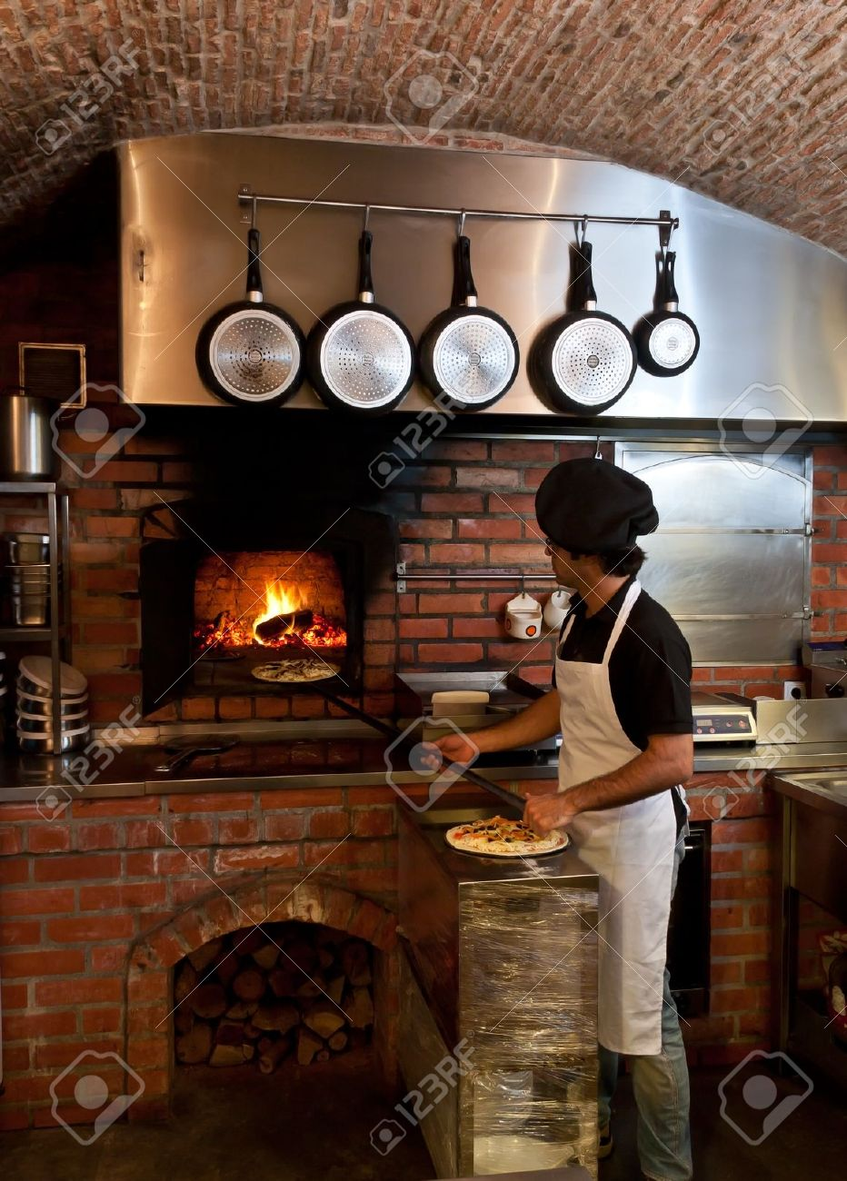 pizza chef puts the pizza inside the wood oven to bake stock photo