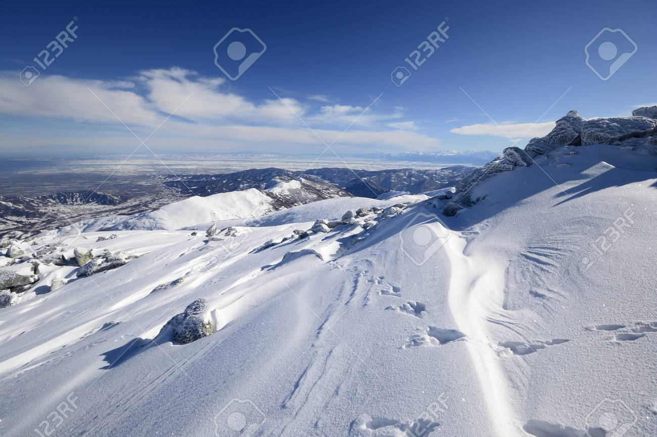 Wide angle view of the alpine arc in Piedmont, Italy, with windswept snowdrift in the foreground Stock Photo - 17512358