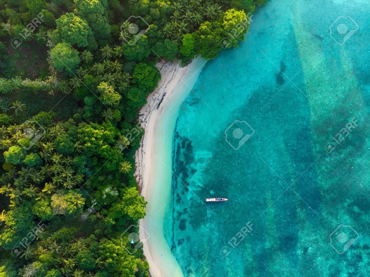 Aerial top down view tropical paradise pristine beach rainforest blue lagoon at Banda Island, Pulau Ay. Indonesia Moluccas archipelago, top travel destination, best diving snorkeling. - 122211059