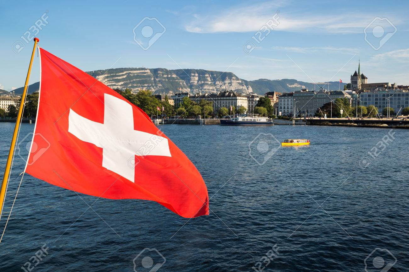A swiss flag floating in the wind over the Lake Geneva, with the city of Geneva in the background Stock Photo - 46559361