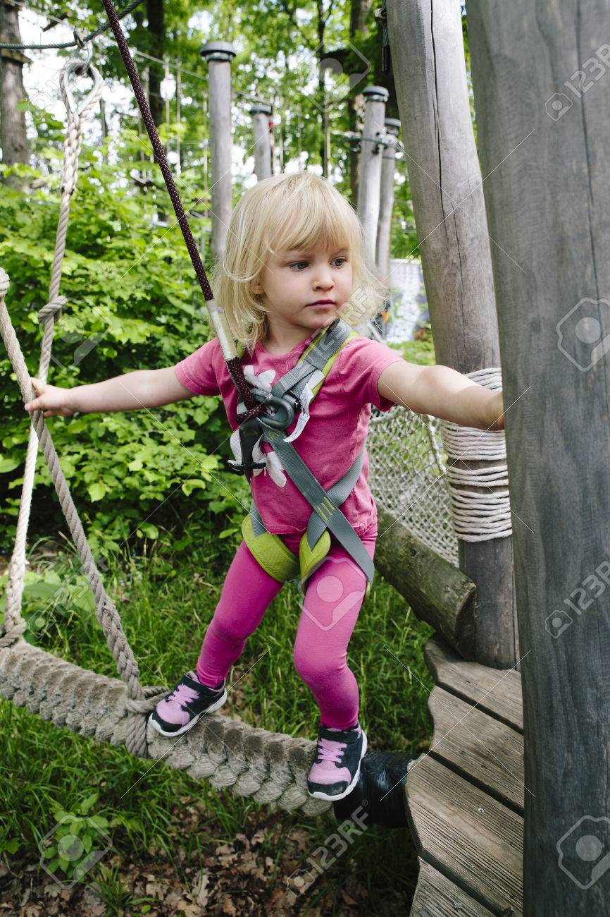 Young blond girl doing a ropes course in an adventure park. Stock Photo - 78888413