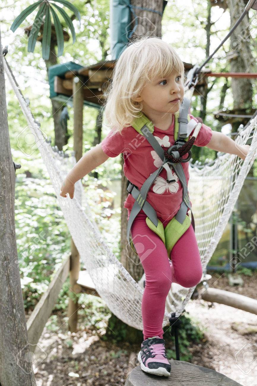 Young blond girl doing a ropes course in an adventure park. Stock Photo - 78888414