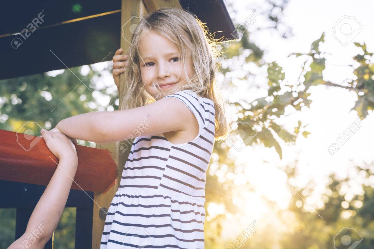Blond girl at a playground. Stock Photo - 79713172