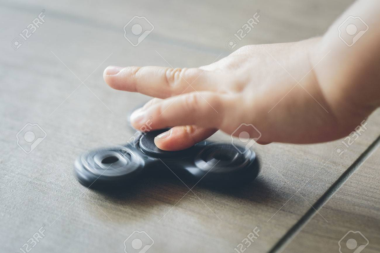 Closeup of a child's hand playing with a fidget spinner Stock Photo - 81817613