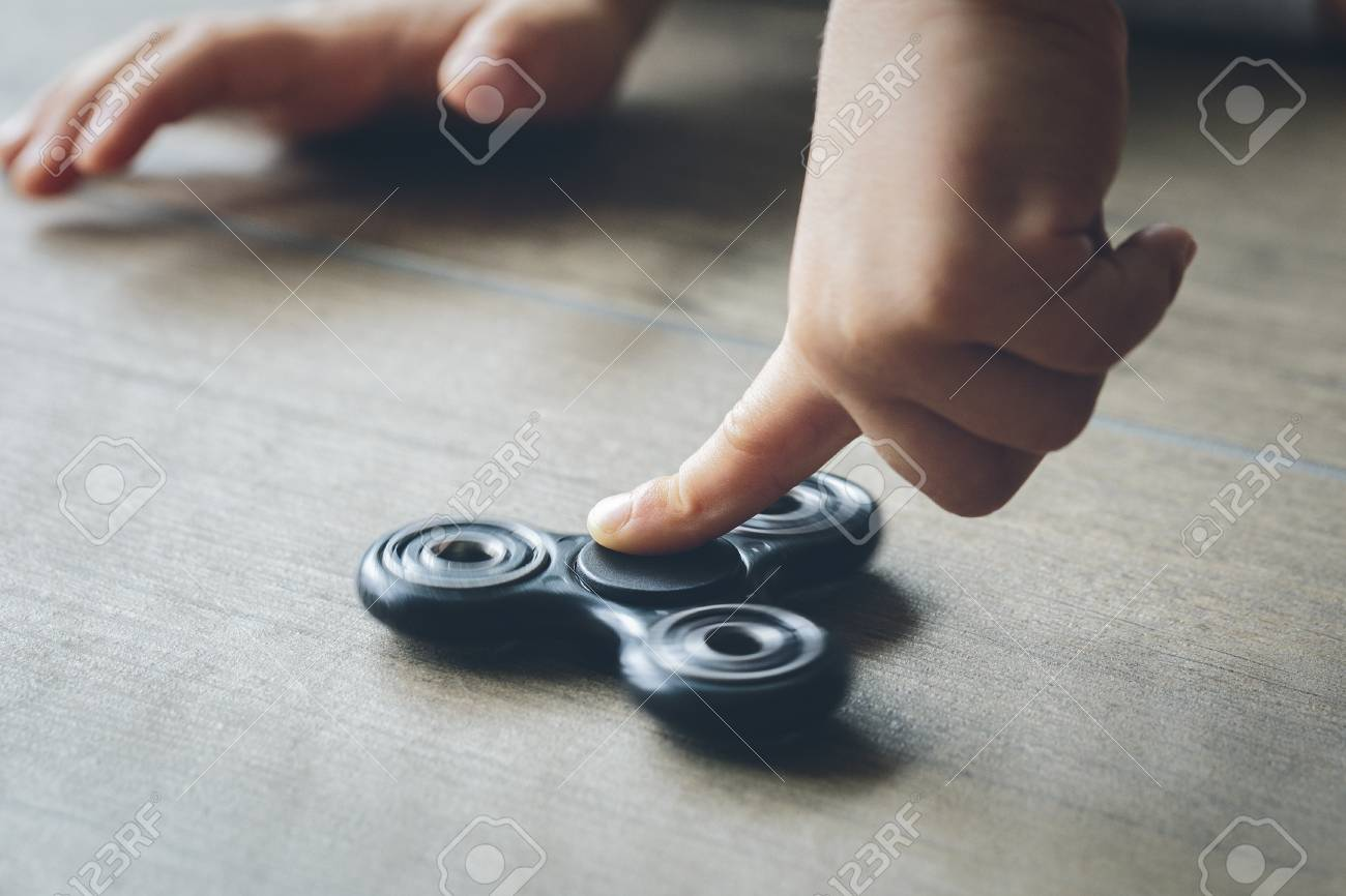 Closeup of a child's hand playing with a fidget spinner Stock Photo - 81427128