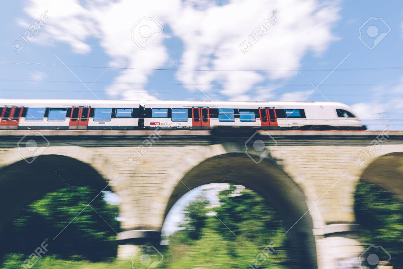 Geneva, Switzerland - June 25, 2017: Swiss regional train passing over a bridge in the Geneva Canton region, with motion blur. Stock Photo - 81827950