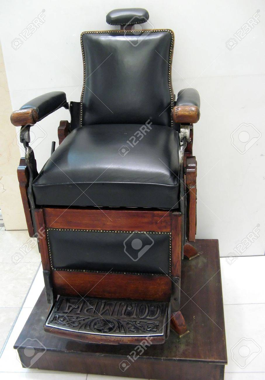 An Old Decorative Shoe Cleaning Chair With Wood And Black Leather